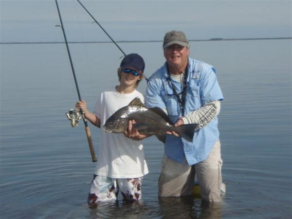 man & boy with black drum